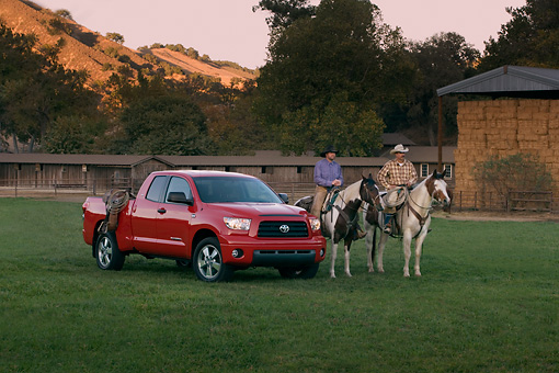 AUT 14 RK1271 01 © Kimball Stock 2007 Toyota Tundra Double Cab SR5 Red 3/4 Front View On Grass By Wranglers On Horses