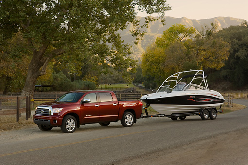 AUT 14 RK1278 01 © Kimball Stock 2007 Toyota Tundra Crewmax Red Pearl 3/4 Side View With Boat On Pavement By Trees