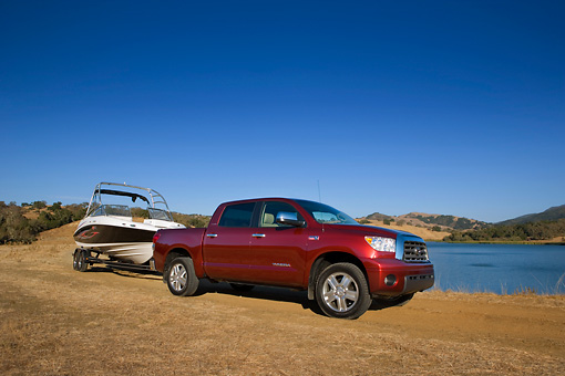 AUT 14 RK1281 01 © Kimball Stock 2007 Toyota Tundra Crewmax Red Pearl 3/4 Side View With Boat On Sand By Water