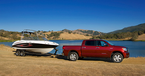 AUT 14 RK1282 01 © Kimball Stock 2007 Toyota Tundra Crewmax Red Pearl 3/4 Front View With Boat On Sand By Water And Hills