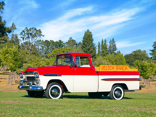AUT 14 RK1388 01 © Kimball Stock 1959 Chevrolet Apache Deluxe Pickup Truck Red And White 3/4 Front View On Grass By Trees