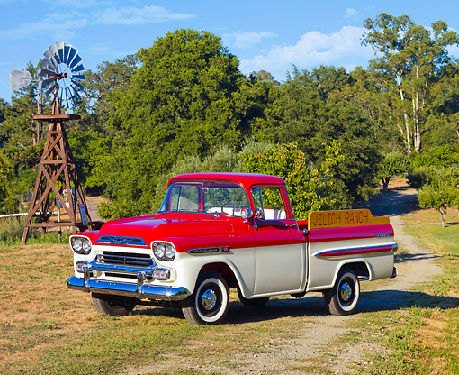AUT 14 RK1391 01 © Kimball Stock 1959 Chevrolet Apache Deluxe Pickup Truck Red And White 3/4 Front View On Grass By Trees