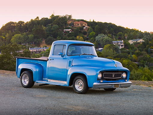 AUT 14 RK1399 01 © Kimball Stock 1956 Ford F-100 Pickup Truck Blue 3/4 Front View On Pavement By Hill