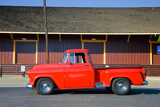 AUT 14 RK1406 01 © Kimball Stock 1957 Chevrolet Stepside Pickup Truck Red Profile View On Pavement By Building