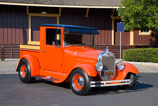 AUT 14 RK1407 01 © Kimball Stock 1928 Ford Model A Pickup Truck Orange 3/4 Front View On Pavement By Building