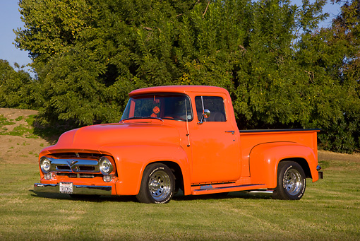 AUT 14 RK1412 01 © Kimball Stock 1956 Ford F-100 Pickup Truck Orange 3/4 Front View On Grass By Trees