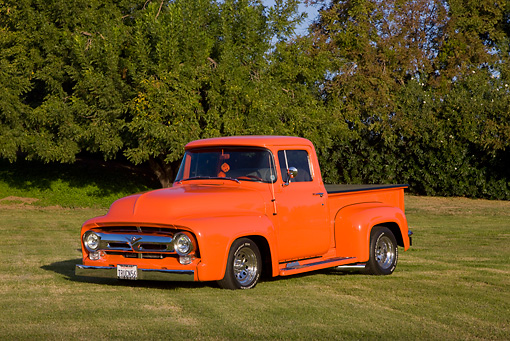 AUT 14 RK1413 01 © Kimball Stock 1956 Ford F-100 Pickup Truck Orange 3/4 Front View On Grass By Trees