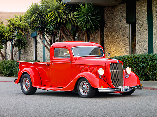 AUT 14 RK1422 01 © Kimball Stock 1935 Ford Pickup Truck Red 3/4 Front View On Pavement By Building And Trees