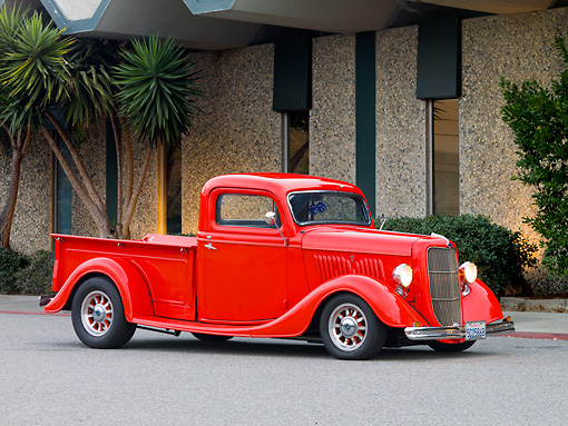 AUT 14 RK1423 01 © Kimball Stock 1935 Ford Pickup Truck Red 3/4 Front View On Pavement By Building And Trees
