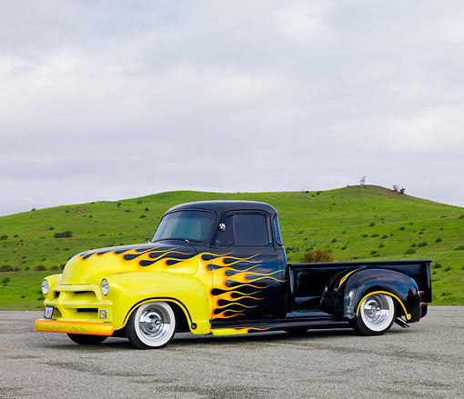 AUT 14 RK1465 01 © Kimball Stock 1954 Chevrolet Pickup Truck Hot Rod Black With Yellow Flames 3/4 Front View On Pavement By Hills