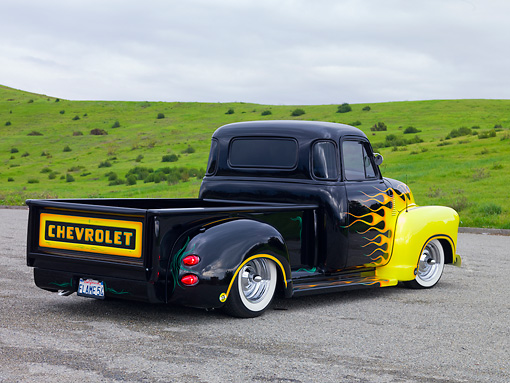 AUT 14 RK1466 01 © Kimball Stock 1954 Chevrolet Pickup Truck Hot Rod Black With Yellow Flames 3/4 Rear View On Pavement By Hills
