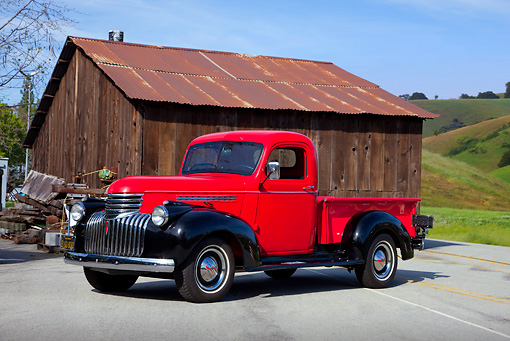 AUT 14 RK1481 01 © Kimball Stock 1946 Chevrolet Pickup Truck Red And Black 3/4 Front View On Pavement By Barn