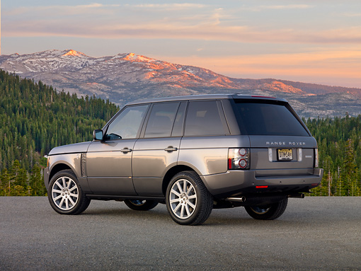 AUT 15 BK0003 01 © Kimball Stock 2012 Land Rover Range Rover Gray 3/4 Rear View On Gravel By Trees And Mountains