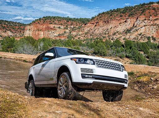 AUT 15 BK0055 01 © Kimball Stock 2015 Range Rover White 3/4 Front View Driving Out Of Muddy Water