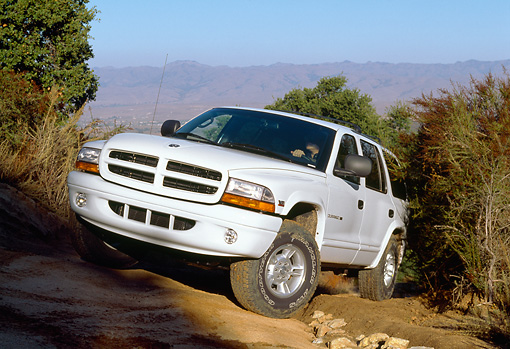 AUT 15 RK0104 05 © Kimball Stock 1999 Dodge Durango SLT White Slanted 3/4 Front View On Dirt Hill