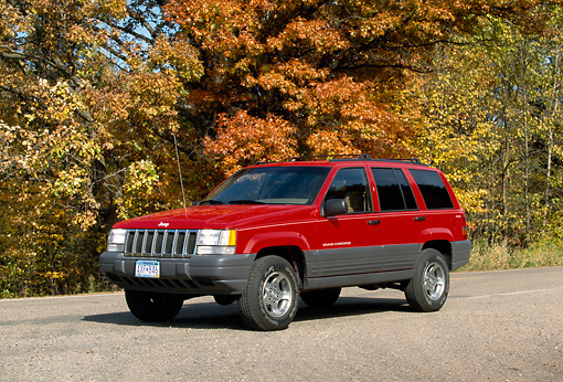 AUT 15 RK0110 01 © Kimball Stock 1998 Jeep Grand Cherokee Red 3/4 Side View On Pavement By Trees