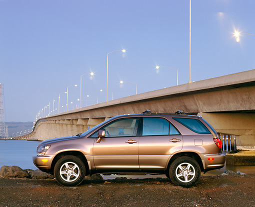 AUT 15 RK0145 07 © Kimball Stock 1999 Lexus RX300 Bronze Profile View By Bridge At Dusk