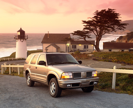 AUT 15 RK0292 16 © Kimball Stock 2000 Oldsmobile Bravada Pewter 3/4 Front View By Lighthouse And Ocean Clouds Parking Lights On