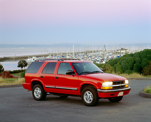AUT 15 RK0312 02 © Kimball Stock 2000 Chevrolet Blazer Red Side 3/4 View On Pavement Harbor Background Filtered