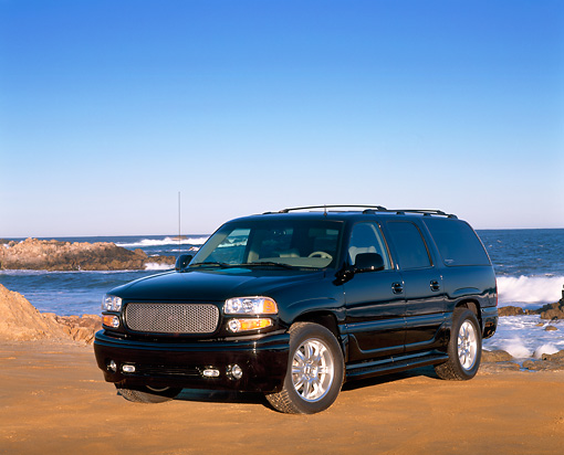 AUT 15 RK0588 09 © Kimball Stock 2002 GMC Denali Canepa Design LE Black 3/4 Front View On Sand By Ocean
