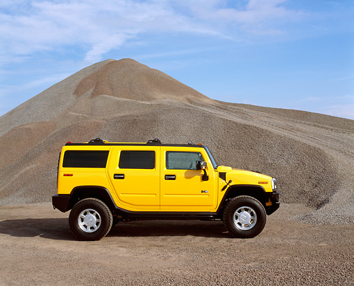 AUT 15 RK0623 05 © Kimball Stock 2003 Hummer Yellow H2 Profile View By Pile Of Gravel Blue Sky