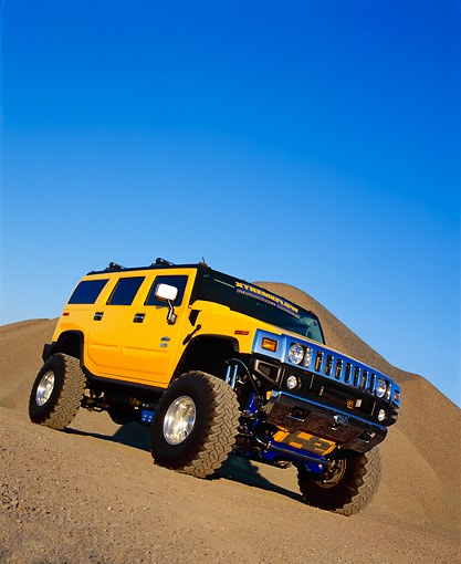 AUT 15 RK0667 03 © Kimball Stock 2003 H2 Hummer Lifted Yellow Slanted Low 3/4 Front View On Dirt Hill Blue Sky