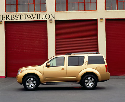 AUT 15 RK0789 01 © Kimball Stock 2005 Nissan Pathfinder Gold Profile View On Pavement By Garage Doors