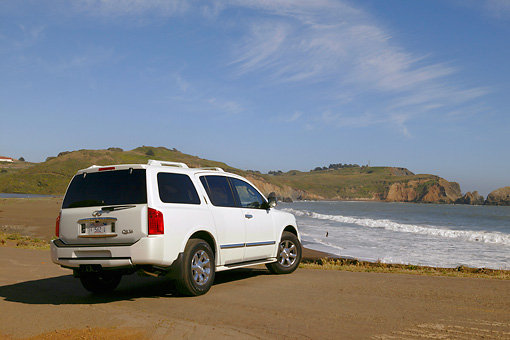 AUT 15 RK0801 01 © Kimball Stock 2004 Infiniti QX56 White 3/4 Rear View On Sand By Ocean