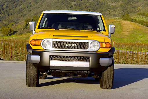 AUT 15 RK1015 01 © Kimball Stock 2007 Toyota FJ Cruiser Yellow And White Low Head On View On Pavement By Grass Hills