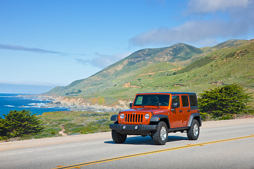 AUT 15 RK1227 01 © Kimball Stock 2011 Jeep Wrangler Rubicon Orange 3/4 Front View On Road By Beach And Hills