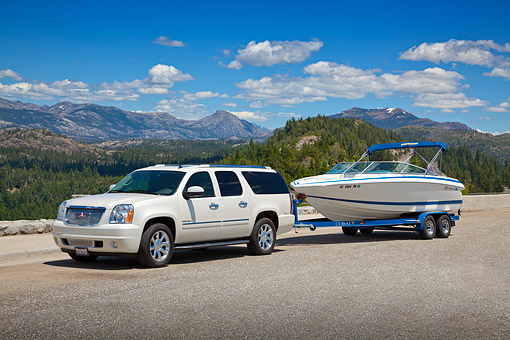 AUT 15 RK1228 01 © Kimball Stock 2011 Yukon Denali White With 226 Cobalt Boat 3/4 Front View On Pavement By Mountains