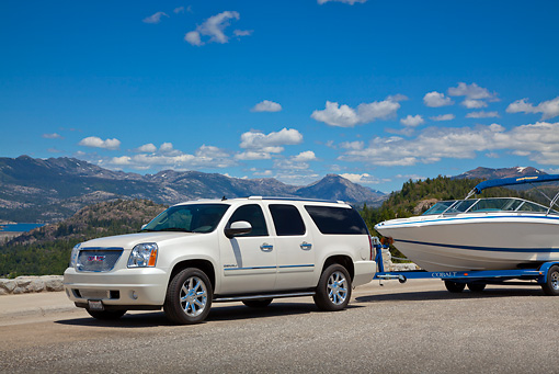 AUT 15 RK1230 01 © Kimball Stock 2011 Yukon Denali White With 226 Cobalt Boat 3/4 Front View On Pavement By Mountains
