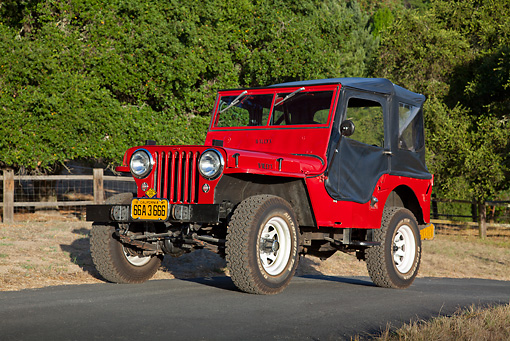 AUT 15 RK1233 01 © Kimball Stock 1947 Jeep CJ-2A Red With Black Top 3/4 Front View On Pavement By Fence And Trees
