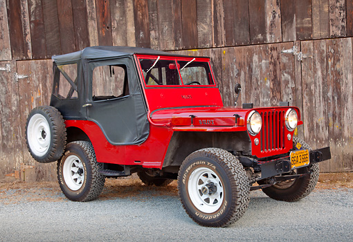 AUT 15 RK1234 01 © Kimball Stock 1947 Jeep CJ-2A Red With Black Top 3/4 Front View On Gravel By Wooden Shed