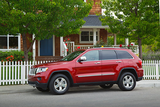 AUT 15 RK1255 01 © Kimball Stock 2012 Jeep Grand Cherokee Limited 4X4 Red Profile View On Pavement By House
