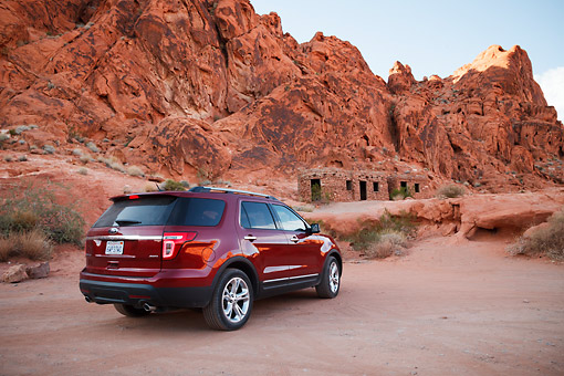 AUT 15 RK1258 01 © Kimball Stock 2013 Ford Explorer Red 3/4 Rear View On Dirt Road By Red Rock