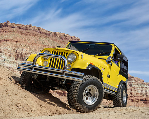 AUT 15 RK1359 01 © Kimball Stock 1985 Jeep CJ7 Yellow 3/4 Front View Driving Over Dirt In Desert