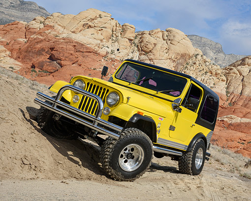 AUT 15 RK1360 01 © Kimball Stock 1985 Jeep CJ7 Yellow 3/4 Front View Driving Over Dirt In Desert