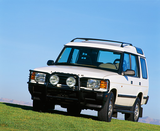 AUT 15 RK0002 07 © Kimball Stock 1996 Land Rover Discovery White 3/4 Front View On Grass Blue Sky