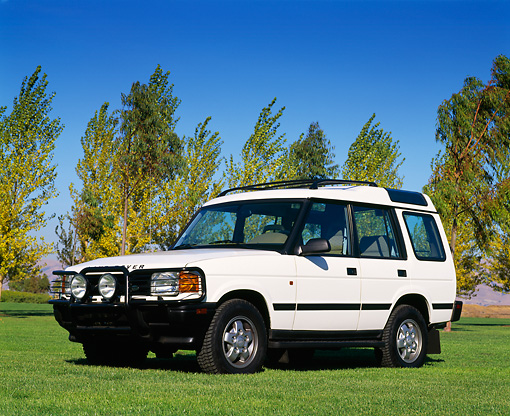 AUT 15 RK0008 04 © Kimball Stock 1996 Land Rover Discovery White Low 3/4 Front View On Grass Trees Blue Sky