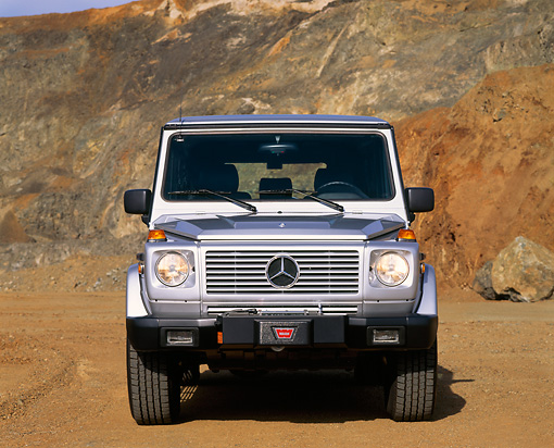 AUT 15 RK0031 02 © Kimball Stock 1997 Mercedes-Benz Gelaendewagen Silver Head On Shot On Dirt