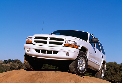 AUT 15 RK0100 01 © Kimball Stock 1999 Dodge Durango SLT White Low 3/4 Front View On Dirt Hill Blue Sky