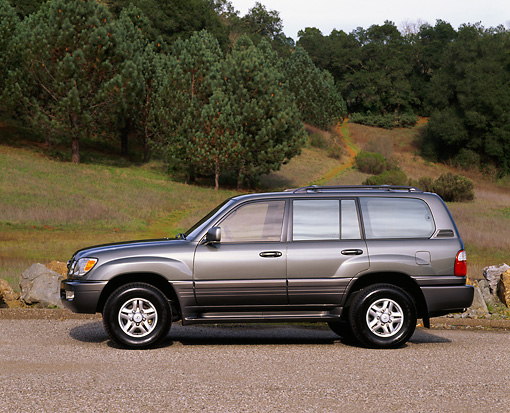 AUT 15 RK0166 06 © Kimball Stock 1999 Lexus LX470 Green Profile View On Pavement By Grass Hill And Trees