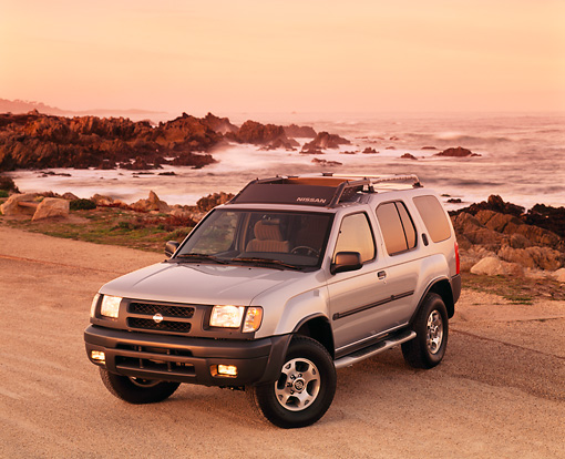 AUT 15 RK0181 05 © Kimball Stock 2000 Nissan Xterra SE Silver Overhead 3/4 Front View On Sand By Ocean And Rocks Headlights On Light Orange Sky