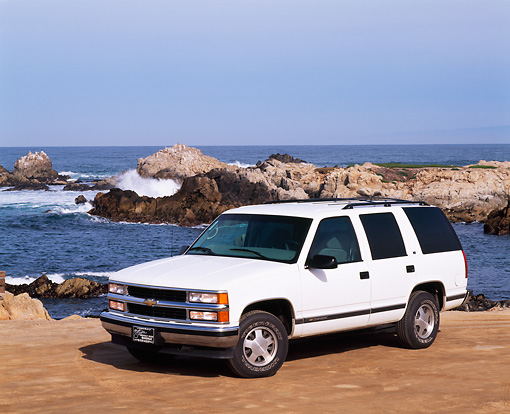 AUT 15 RK0186 08 © Kimball Stock 1999 Chevrolet Tahoe White Front 3/4 Front View On Sand By Ocean And Rocks