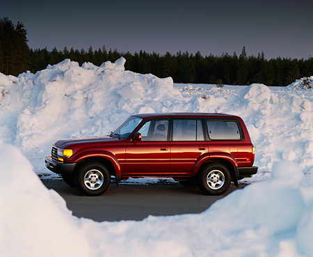 AUT 15 RK0202 03 © Kimball Stock 1995 Toyota Land Cruiser Burgundy 3/4 Front View On Pavement By Snow