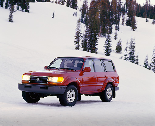 AUT 15 RK0207 06 © Kimball Stock 1995 Toyota Land Cruiser Burgundy 3/4 Front View On Snow Trees