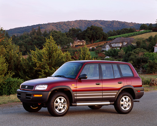 AUT 15 RK0218 03 © Kimball Stock 1996 Toyota Rav4 Burgundy 3/4 Front View On Pavement Trees Background