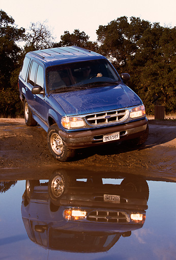 AUT 15 RK0227 05 © Kimball Stock 1996 Ford Explorer Blue 3/4 Front View On Mud By Water Trees Background