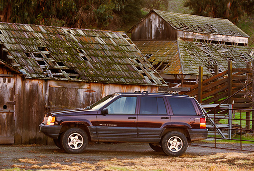 AUT 15 RK0229 02 © Kimball Stock 1996 Jeep Grand Cherokee Burgundy Profile View By Old Barn
